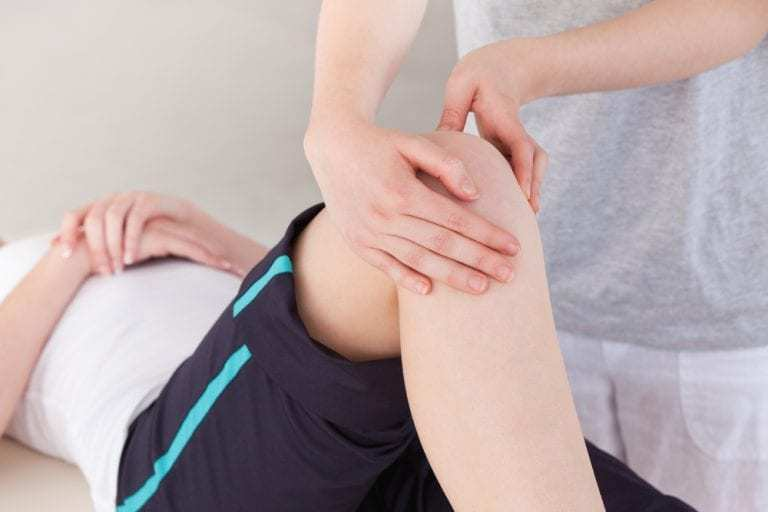 Therapist evaluating the knee of a patient