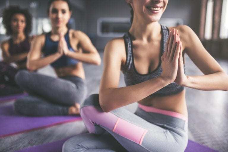 Cropped image of three girls doing yoga together